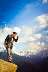 Young businessman looking down from the mountain top