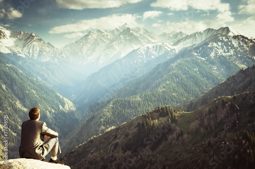 businessman at the top of the mountain sitting and thinking - 77898515