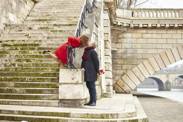 Couple kissing on a Parisian embankment