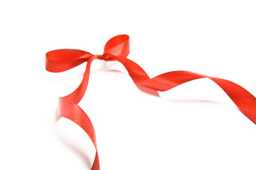 Shiny red satin ribbon and bow on white background