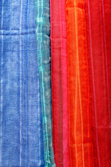 Red and blue scarves at local market, India