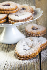 Linzer cookies sprinkled with powdered sugar.