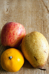 An apple, an orange and a pear on a tabletop.