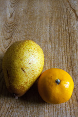 An orange and a pear displayed side by side