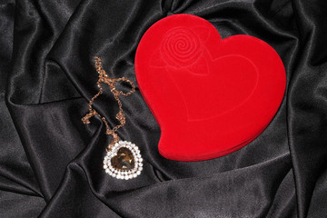 Red heart-shaped jewelry box  on a black silk
