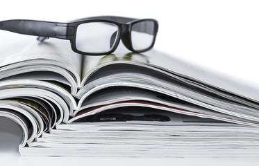 Brille auf Zeitungsstapel