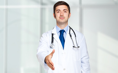 Portrait of a friendly doctor giving you his hand