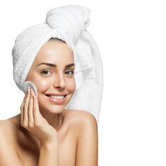 Smiling woman with a towel on her head, removes makeup