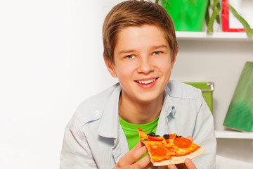 Happy boy holding pizza piece and eating at home