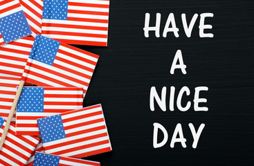 The phrase Have A Nice Day on a blackboard with flags
