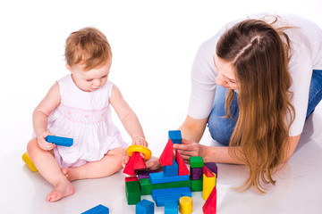 Beautiful baby with mother building with cubes