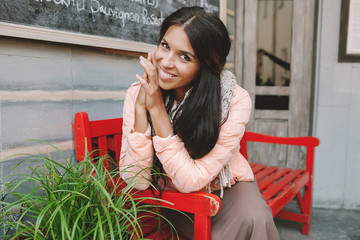 Young beautiful woman smiling sitting at red bench