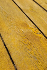 Old weathered pine boards being yellow painted