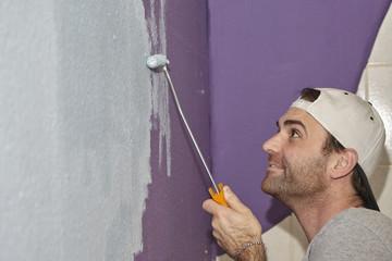Maler beim streichen und renovieren eines Zimmers