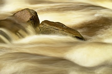 Slippery boulders in mountain stream. Clear blurred water