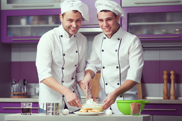 Tiramisu cooking concept. Portrait of two smiling men cooking