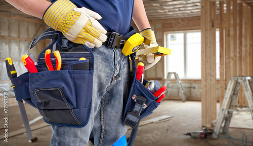 Worker with construction tools. - 77907919