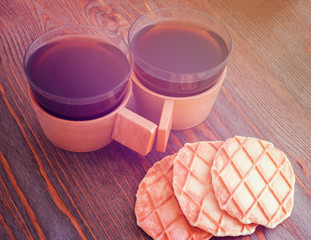 2 cups of coffee on a wooden background and waffles