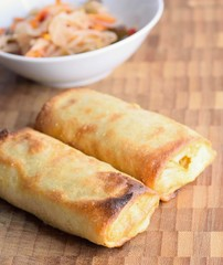 Chinese spring rolls on a wooden plate with vegetable salad.