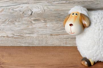 Schaf vor Holzhintergrund mit Freitextraum