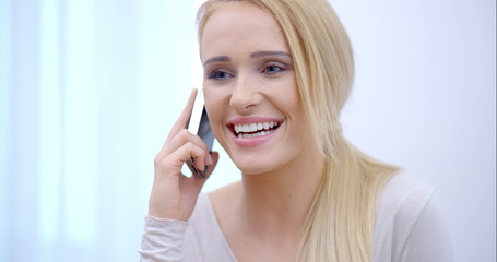 Pretty blond woman listening to a mobile call