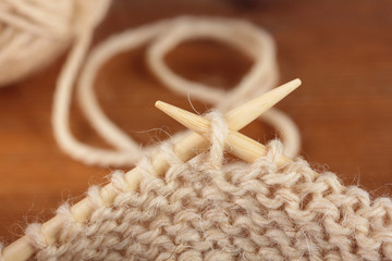 Two bamboo knitting needles in process of knitting