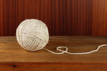 Ball of rough rustic yarn on dark wooden background