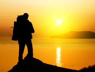 tourist on sundown background.