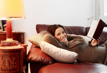 smiling girl in relax over sofa with a book