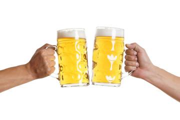 zwei Männerhände stoßen mit Bier an
