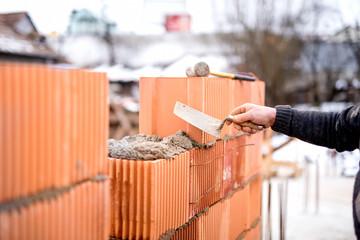 Construction bricklayer worker building walls with fresh bricks
