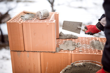 man working with bricks and cement, building walls