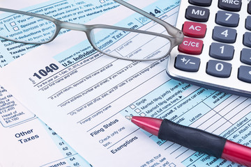 2014 IRS form 1040 with calculator and pen