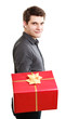 Holiday. Man giving red gift box with golden ribbon