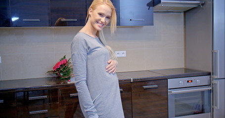 Happy Pregnant Woman Standing at the Kitchen Area