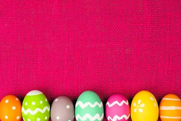 Easter egg bottom border over pink burlap background
