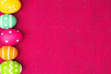 Colorful Easter egg side border over pink burlap background