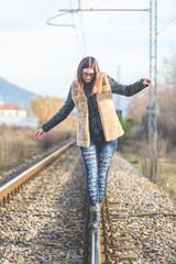 Beautiful Young Woman Walking in Balance on Railway Tracks. The