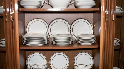Brown shelf with vintage porcelain tableware