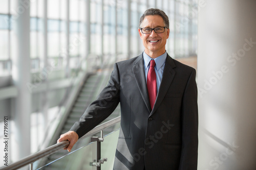 Handsome mature businessman with glasses smiling - 77916921