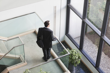 Businessman pauses on stairway in office building