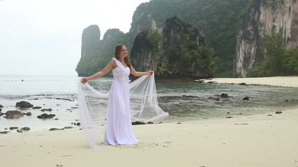 young blonde girl smiling demonstrates her wedding dress standin