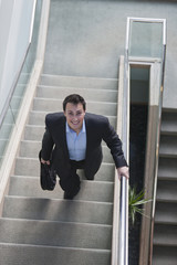 Businessman walking up stairs in office building