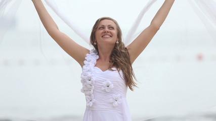 blonde bride in wedding dress veil waving like wings stand baref