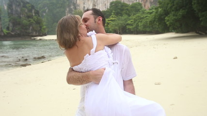 strong groom carries blonde bride in his arms and kisses at sand