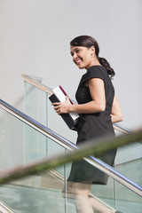 Businesswoman walking up on stairs of office building