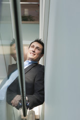 Businessman leaning on the stairwell of an office building