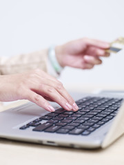 woman entering credit card number using laptop