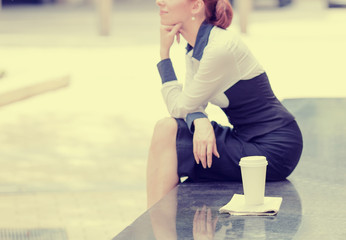lonely woman sitting outside corporate office