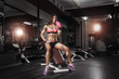 canvas print picture - fitness girl with shaker posing on bench in the gym